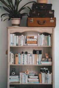 Books on a brown wooden shelf - Taryn Elliot